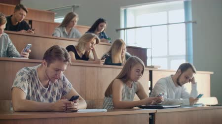 correspondência : Students in a large audience look at the screens of smartphones and do not communicate in real life, write messages only online.