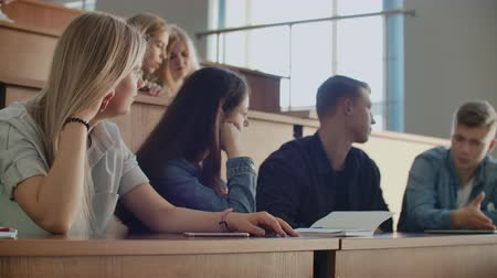 collegezaal : The group of cheerful happy students sitting in a lecture hall before lesson. The group of cheerful students sitting in a lecture hall before lesson Stockvideo