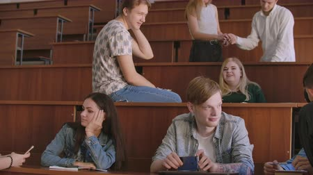 faculty : The group of cheerful happy students sitting in a lecture hall before lesson. The group of cheerful students sitting in a lecture hall before lesson Stock Footage