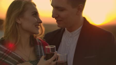 kırmızı şarap : Young married couple on the roof hugging and drinking red wine from glasses standing dressed in plaid and admiring the beautiful sunset over the city.