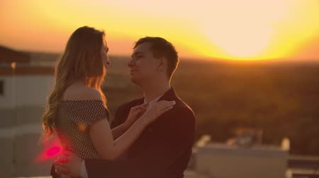 velkolepý : A man and a woman embrace on a rooftop at sunset