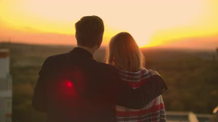 péntek : Lovers embracing guy girl watching the sunset with wine standing on the roof of the building. Slow motion picture of the relationship of a married young couple Stock mozgókép
