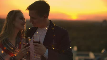 pátek : Young married couple on the roof hugging and drinking red wine from glasses standing dressed in plaid and admiring the beautiful sunset over the city.