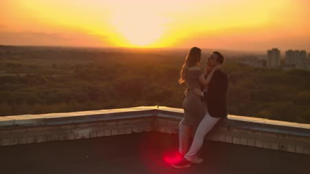 adore : A man and a woman embrace on a rooftop at sunset