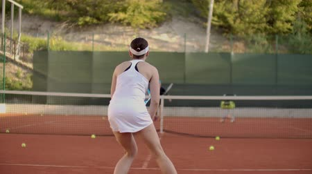 ütő : Woman tennis player practicing hitting the ball with the coach, hitting the ball with a racket in slow motion. Professional tennis player training