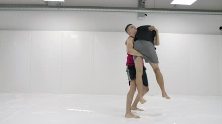 worstelaar : Two male wrestlers in a white room work out throwing mats. Take a grapple and throw through yourself