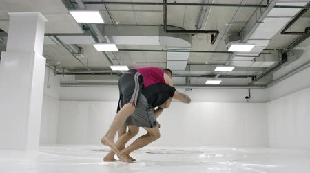 worstelaar : Two wrestlers perform in slow motion. Greco-Roman wrestlers train in the hall in T-shirts and coats. Stockvideo