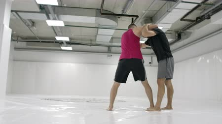 grappling : MMA fighters practice wrestling techniques. White hall and wrestlers on the tatami. A man in a red T-shirt and a man in a check T-shirt. Coach and fighter practice captures and throws