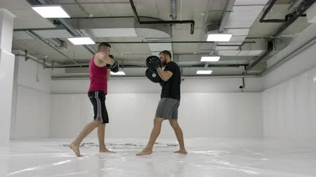 łokieć : By fighting a mma with a trainer, he works out the striking technique of arms and legs, training the reaction of dives and deviations from strikes. Workout with a partner on the paws of blows Wideo