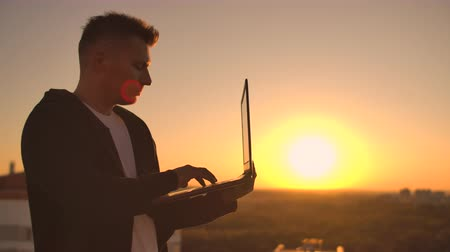 A male stockbroker freelancer stands on a rooftop at sunset with a laptop and types on a keyboard with his fingers looking at the cityscape from a birds eye view
