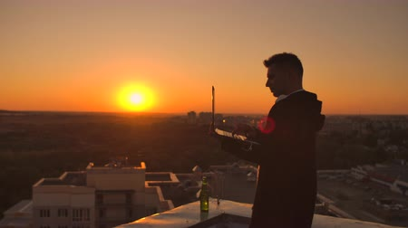 senha : A male stockbroker freelancer stands on a rooftop at sunset with a laptop and types on a keyboard with his fingers looking at the cityscape from a birds eye view