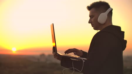 computer programmer : A man freelancer in headphones standing on the roof at sunset writes on the keyboard code pages. Little business. Listen to music and work at the computer enjoying the beautiful view from the roof Stock Footage