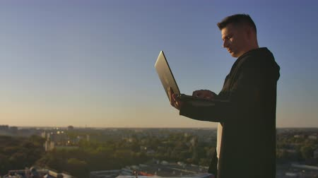 contraseña : Programmer a hacker is on the roof with a laptop at sunset says error code on the keyboard and looking at the city view