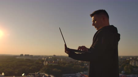 senha : Programmer a hacker is on the roof with a laptop at sunset says error code on the keyboard and looking at the city view