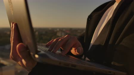 remotely : Close-up: a programmers hand typing on a laptop keyboard at sunset overlooking the roof. A businessman works remotely. Freelancer performs work on vacation.