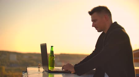 malware : A male stockbroker freelancer stands on a rooftop at sunset with a laptop and types on a keyboard with his fingers looking at the cityscape from a birds eye view