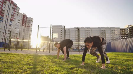 hurken : Man and woman in sportswear at sunset jumping burpee, yelling exercises for health and weight loss against the background of city buildings.