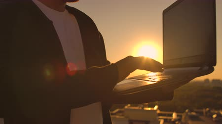 A male freelance programmer sits on a skyscraper roof with a laptop and beer typing code on a keyboard during sunset. Remote work.