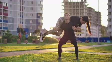 squatting : A man squats with a girl sitting on his shoulders in a city Park against a backdrop of buildings at sunset in slow motion.