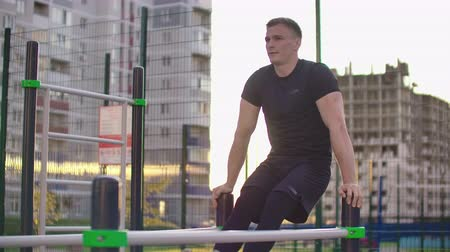 párhuzamos : Sporty man in black clothes performs lifting legs on parallel bars in slow motion against the background of buildings in the city Park Stock mozgókép