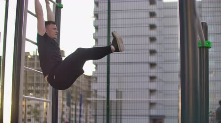 buikspieren : A man performs a leg lift on parallel bars in slow motion against the background of buildings in a city Park Stockvideo