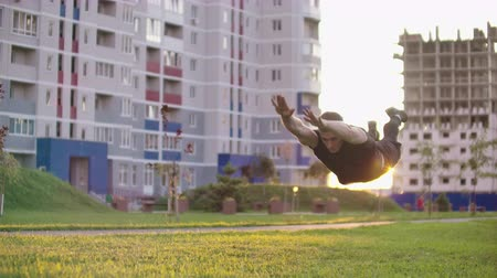 難しさ : An athlete doing extreme push up and backflips and pushups at sunset in slow motion the background of the city 動画素材