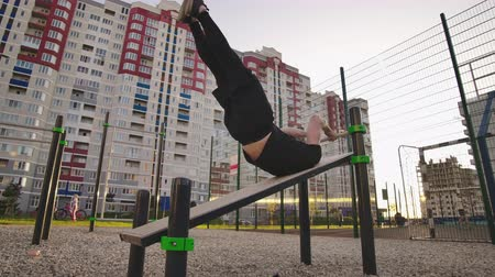 гимнаст : Strong fit man workout out on horizontal bars outdoors. Young man training abdominal muscles lifting legs high to the. Head doing push ups outdoors during the