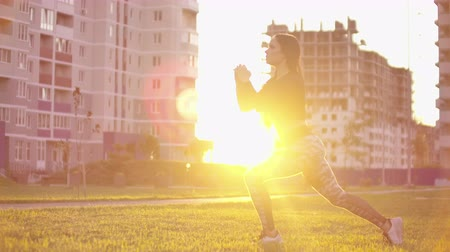 trabalhar fora : young fit and energetic woman doing sport workout and fitness lunge exercises with weights for healthy lifestyle in city park during sunset.
