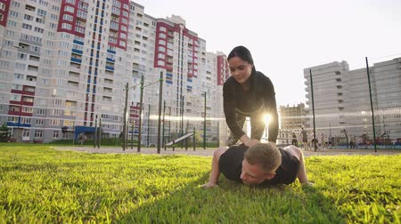 construção muscular : Guy and girl push-ups outdoors. Male and female doing exercises together outdoor. Couple doing sport keeping the body in tension, leaning on the extended arms.