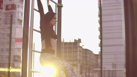 elevação : SLow motion: Candid shot of real healthy and fit woman performing hanging leg raises on outdoor fitness station in sunset at city park. Showing strong abdominal six-pack. Stock Footage