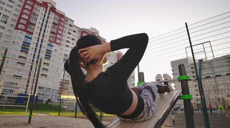 retorcido : Doing twisting crunches. Serious confident sporty young woman sitting on wooden bench and doing twisting crunches at sports ground. Stock Footage