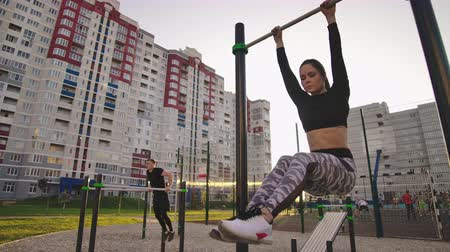 raises : SLow motion: Candid shot of real healthy and fit woman performing hanging leg raises on outdoor fitness station in sunset at city park. Showing strong abdominal six-pack. Stock Footage