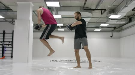 킥복싱 : Coach and kick-boxers practice kicks in the jump with rotation on the paws in slow motion