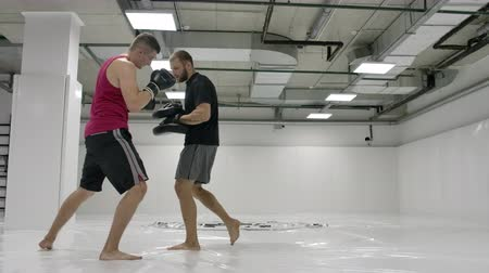 kickbox : The coach and the fighter work out the kick in the jump knee on the paws in slow motion. Training for kickboxing
