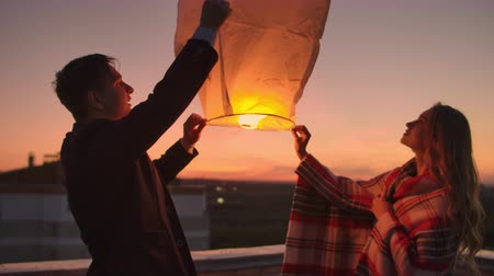 adore : A man and a girl in a plaid launch a sky lantern on the roof