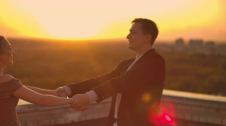 meghittség : A man and a woman in love dance standing on the roof of a building at sunset looking at each other Stock mozgókép