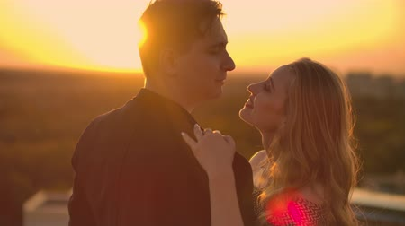 adore : A man and a woman in love dance standing on the roof of a building at sunset looking at each other Stock Footage
