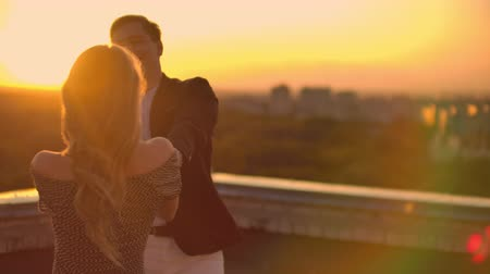adore : Two lovers a man and a woman laugh and dance on the roof at sunset. Slow motion happy couple summer on the roof
