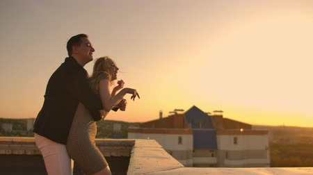 velkolepý : A man with a woman running on the roof holding hands. Slow motion lovers on the roof