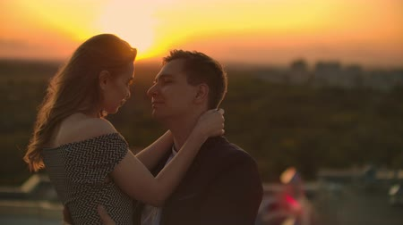 adore : The lovers see eye to eye to each other on the roof at sunset. Romantic couple on the roof Stock Footage