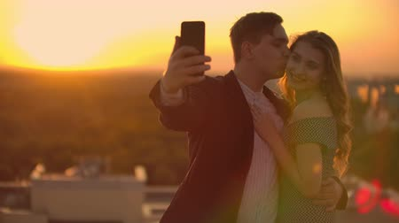adore : Two lovers a man and a woman laugh and take a photo selfie on the phone. Slow motion selfie summer together