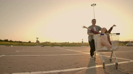 troli : Lens flare: Cheerful people couple man and woman at sunset ride supermarket trolleys in slow motion Stock mozgókép