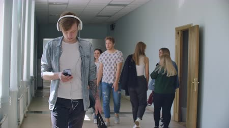 okula geri : A lot of people walk down the hall of the University talking discussing and listening to music. The camera moves between different groups Stok Video