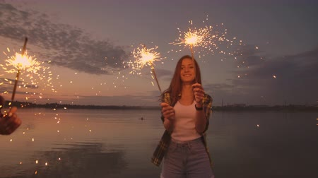 sparklers : Dancing friends with fireworks have fun and celebrate the holiday together guys and girls in the summer on the beach. Sparklers in the hands of people having fun Stock Footage