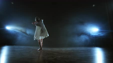 balerína : Modern ballet dancing woman barefoot doing spins and pirouettes and dance steps standing on stage in smoke in slow motion. Performance on stage