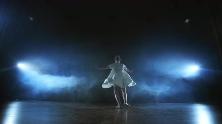 akrobatikus : Modern ballet dancing woman barefoot doing spins and pirouettes and dance steps standing on stage in smoke in slow motion. Performance on stage