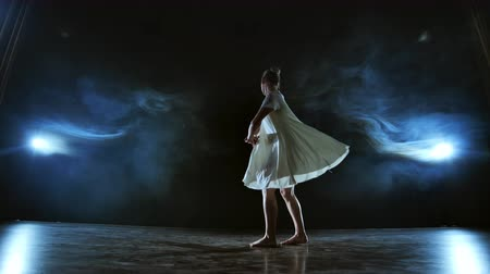 lelkesedés : Elegant ballerina jumping and dancing in barefoot and white loose oversize dress in studio. With smoke. Stock mozgókép