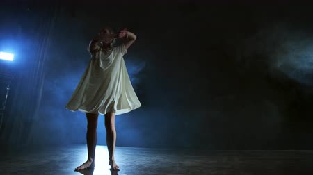 entusiasmo : A young female ballerina barefoot jumps on stage and moves in slow motion in a loose white dress Stock Footage