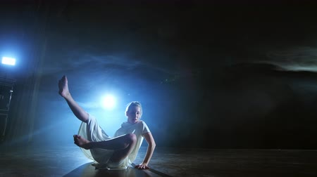 balerína : A young female ballerina barefoot jumps on stage and moves in slow motion in a loose white dress Dostupné videozáznamy