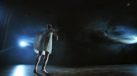 entusiasmo : Elegant ballerina jumping and dancing in barefoot and white loose oversize dress in studio. With smoke. Stock Footage